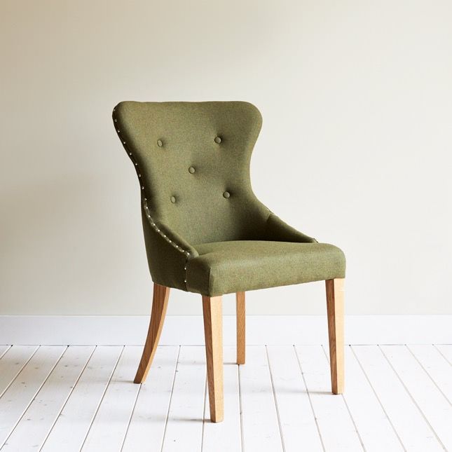 Angled view of Brasserie dining chair in olive green upholstery